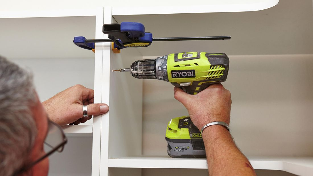 Using a clamp and drill to secure the cabinets in the linen closet