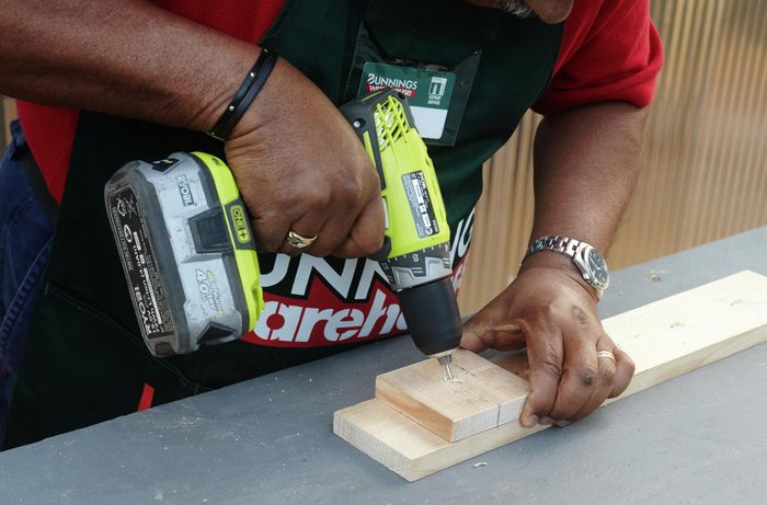 Person drilling hole into timber