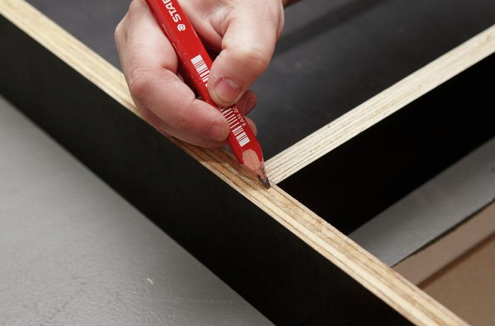 Person marking up form ply frame with pencil.