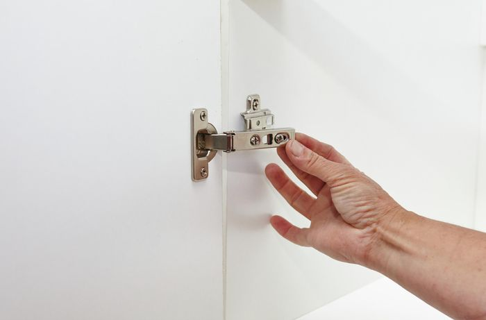 Person attaching doors to cupboard