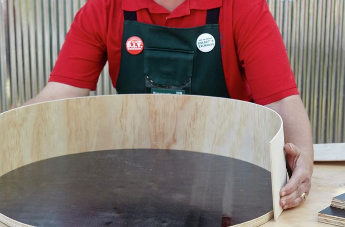 A person curving a strip of plywood around a circular plywood base