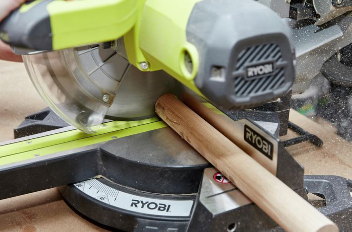 Person cutting timber dowel with circular saw.