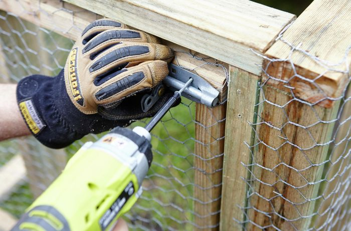 A slide lock being screwed into place on the door of a chicken coop by a Bunnings team member with a power drill