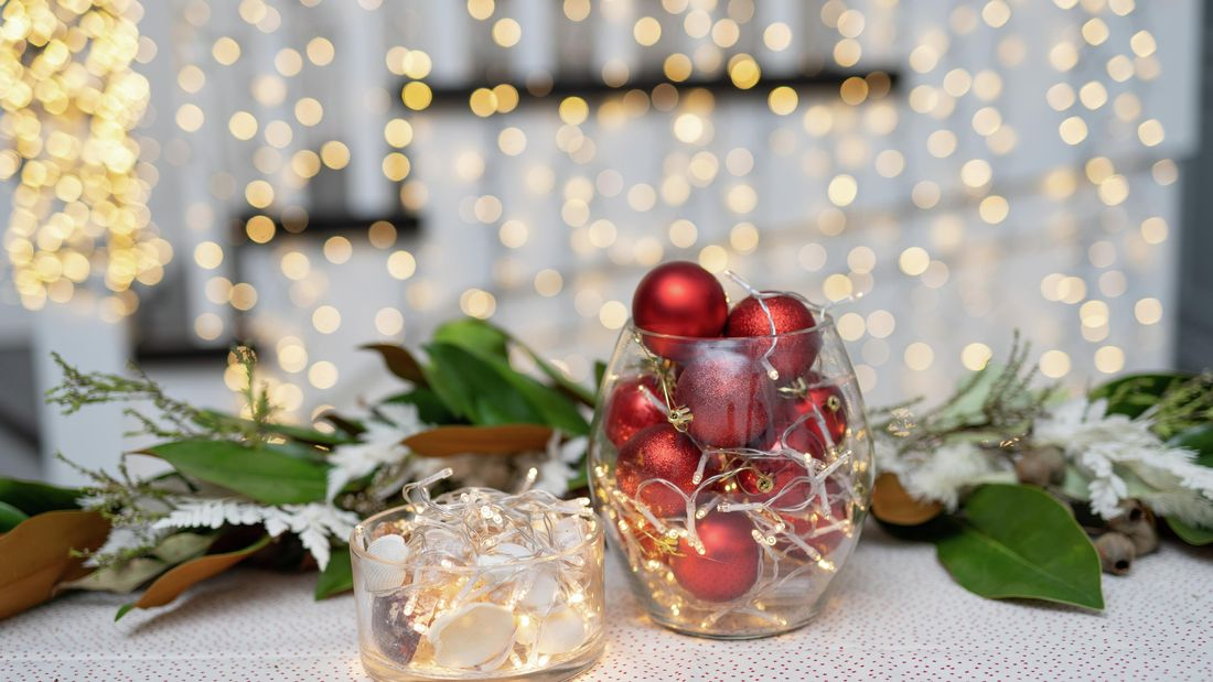 A small glass filled with red baubles and glowing fairylights