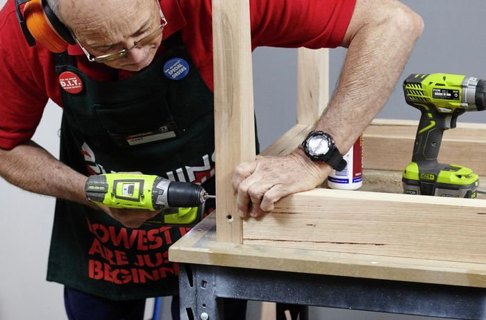 The framework of an outdoor table being assembled by a Bunnings team member