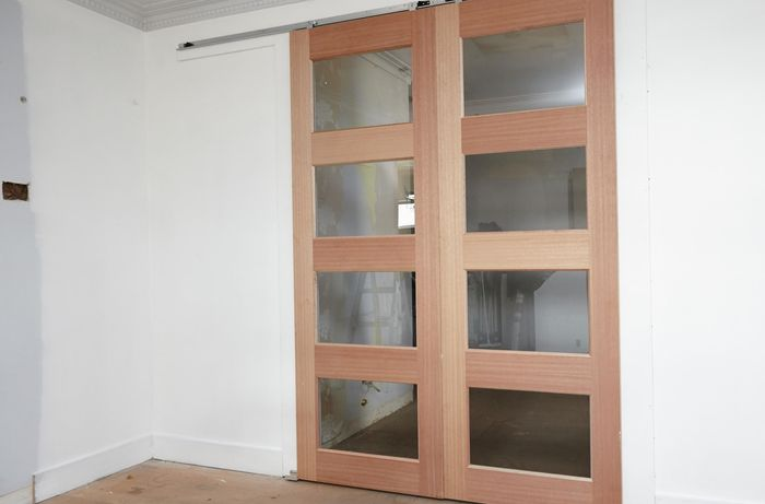 Installed wooden framed sliding doors with glass panels on a white wall