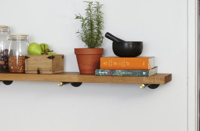 A timber kitchen shelf with jars of food and cookbooks