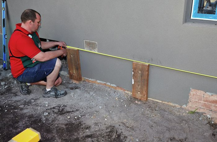 Person measuring length between two support posts.
