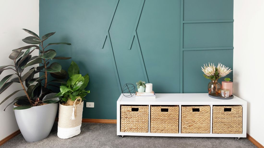 Room with green wall, plants and cube storage unit with wicker basket inserts.