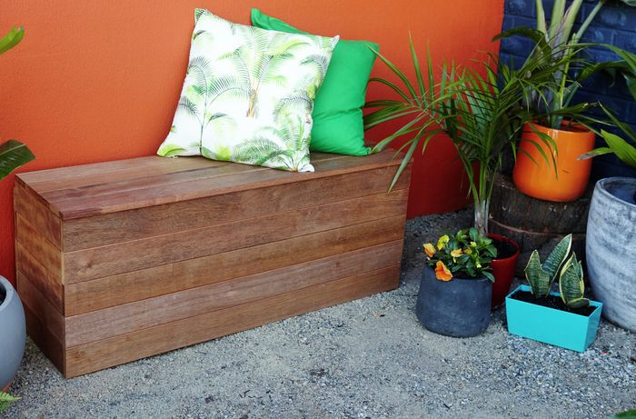 A finished bench seat with cushions and outdoor plants against an orange wall