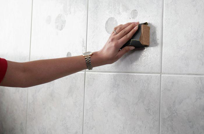 A person sanding bathroom tiles on a wall.