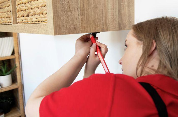Person attaching bracket to shelf