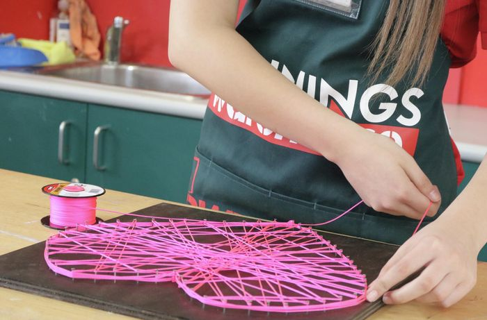 Person threading pink string around nails in plywood sheet