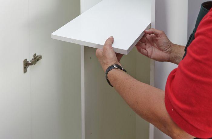 Person placing shelf.