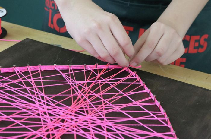 Person threading pink string around a heart shape outline