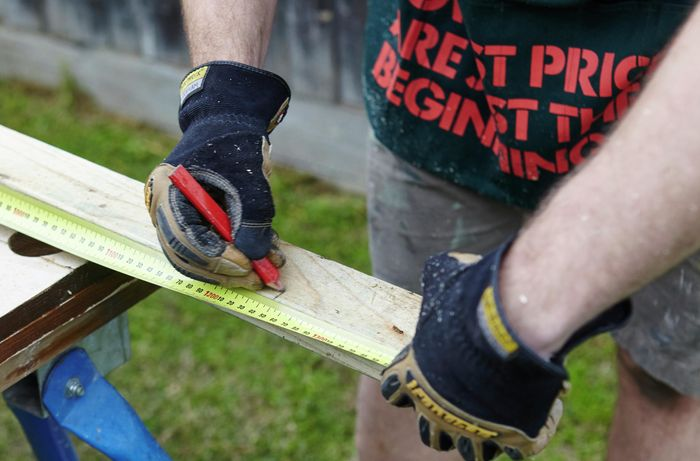 A length of timber being measured and marked for later cutting with a pencil and tape measure