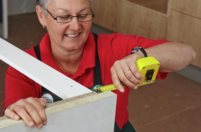 Person using measuring tape to measure cabinet
