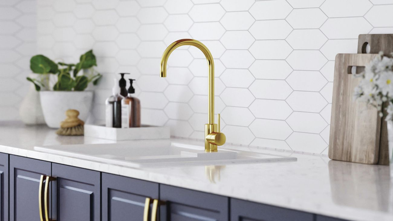 Close up of a kitchen sink area featuring a tiled splashback, brushed brass sink mixer and Kaboodle 'Bluepea' heritage profile cabinetry