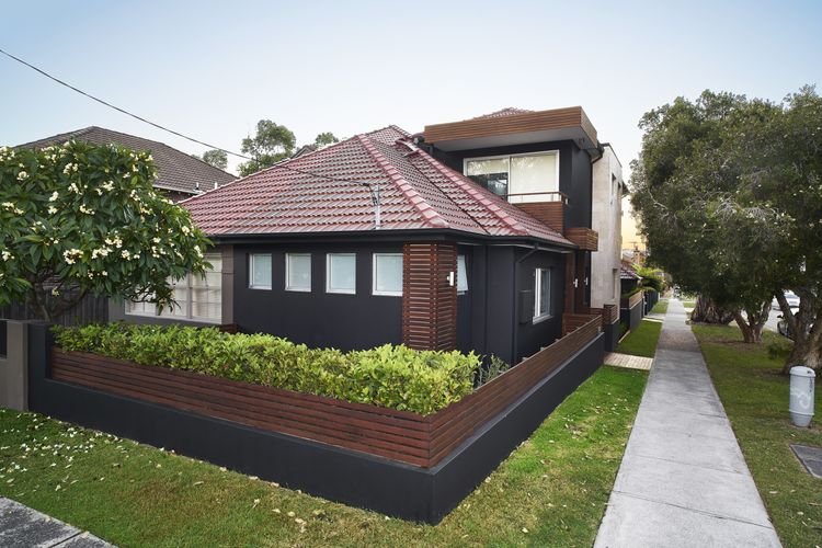 Exterior of renovated older house with extension, all painted charcoal with contrasting decking timber
