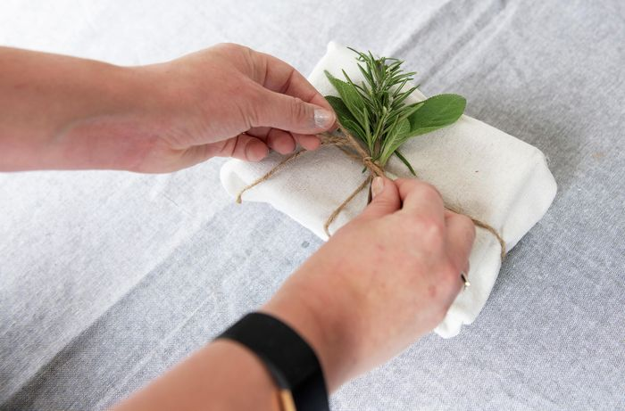 Person tying up present and leaf with string.