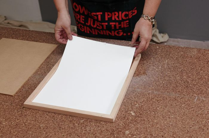 A picture being laid into a home-made wooden picture frame face down