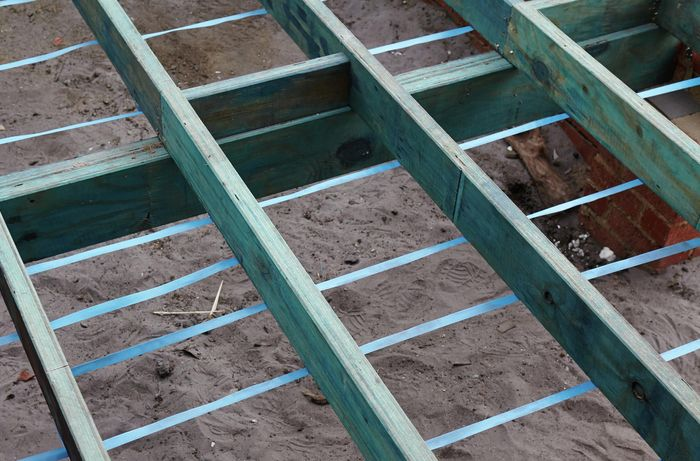 Floor joists with lengths of strapping underneath at regular intervals
