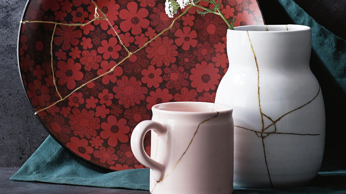 A cup, vase, and flower-patterned plate repaired with kintsugi techniques, each with a vein of gold running through