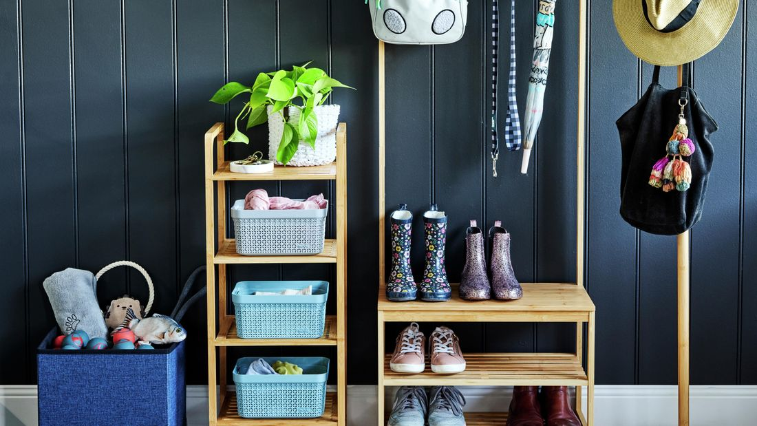 Organised timber shelving rack, with kids boots and shoes and hanging bag and umbrella off hooks. Separate hat stand with hats and small four tier rack with basket organisers.