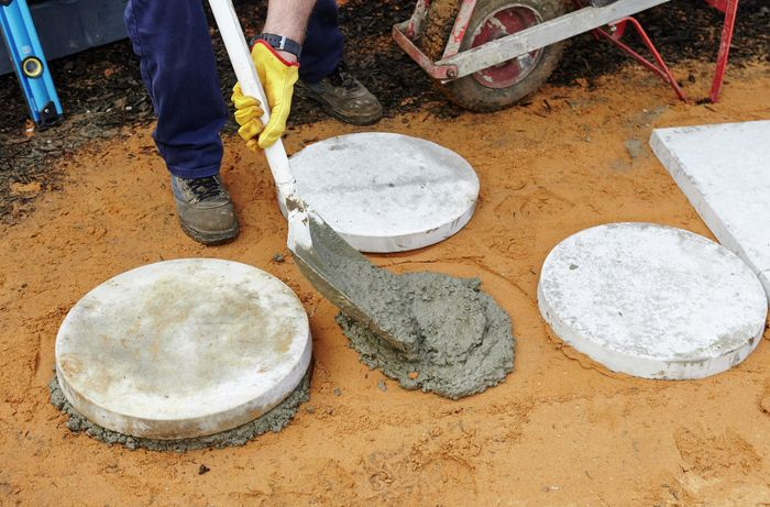 Person shovelling concrete onto a sand base between two pavers