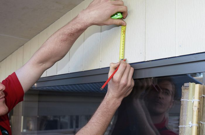 A person measuring above a window on the outside of a house