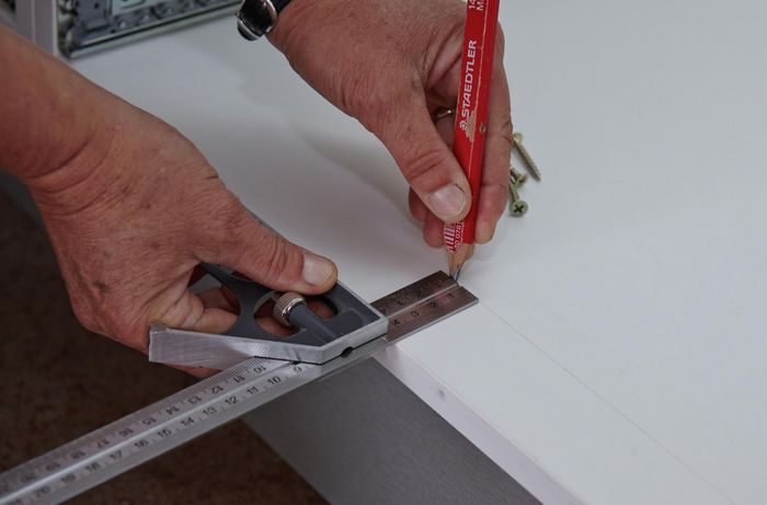 A person marking a measurement on the bottom panel of a cabinet