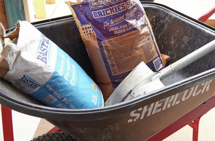 A wheelbarrow holding a shovel, a bag of concrete and a bag of bricklayer's sand