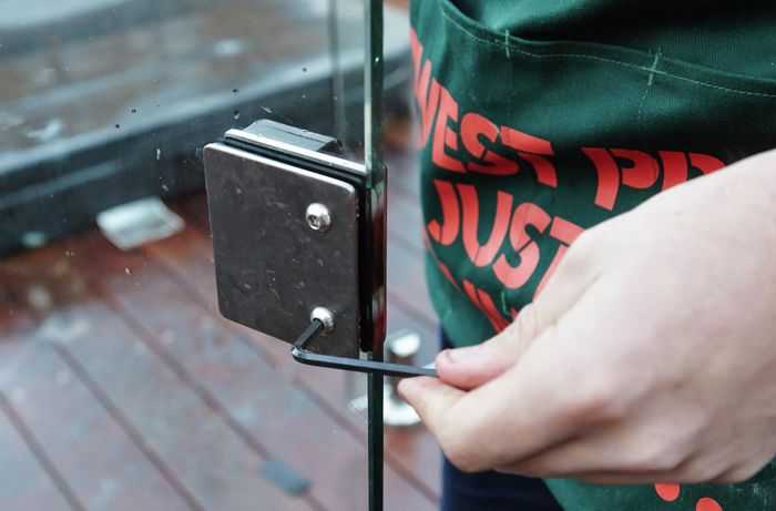 Person using Allen key to tighten hinge plates against gate.