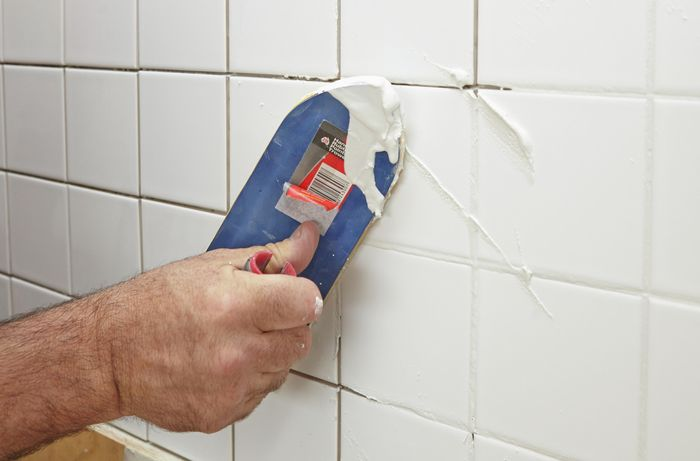 Person using scraper to apply grout to freshly tiled wall.