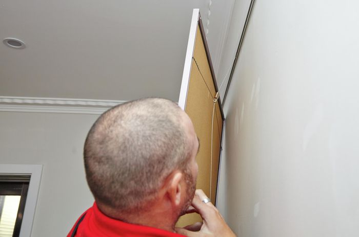 A Bunnings team member checking the length at which the hanging wire is hanging the picture attached to it