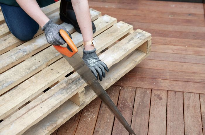 A pallet being dismantled with a saw