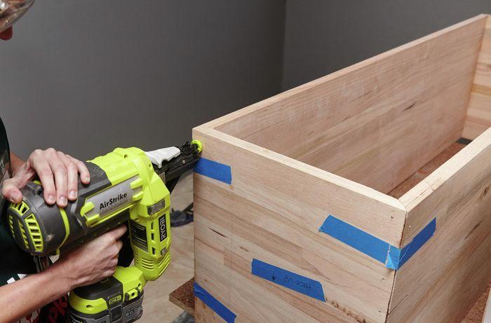 A person attaching an end piece to a timber box using a nail gun