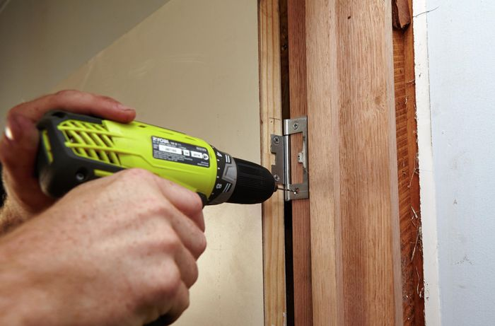 A door hinge being screwed into a doorframe using a power drill