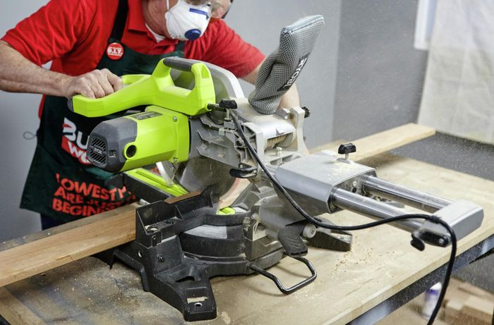 A mitre saw being used to cut a length of timber by a Bunnings team member