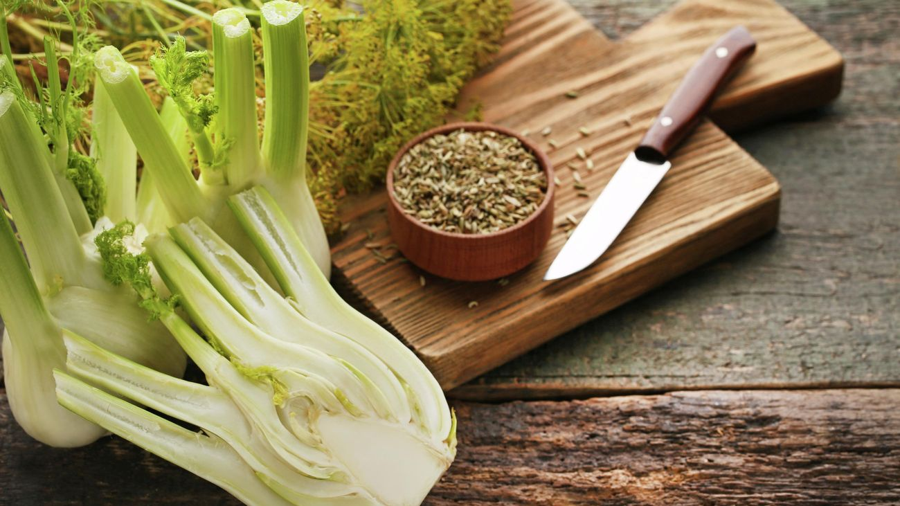 Harvested fennel, one cut in half, and a bowl of fennel seeds on a wooden table