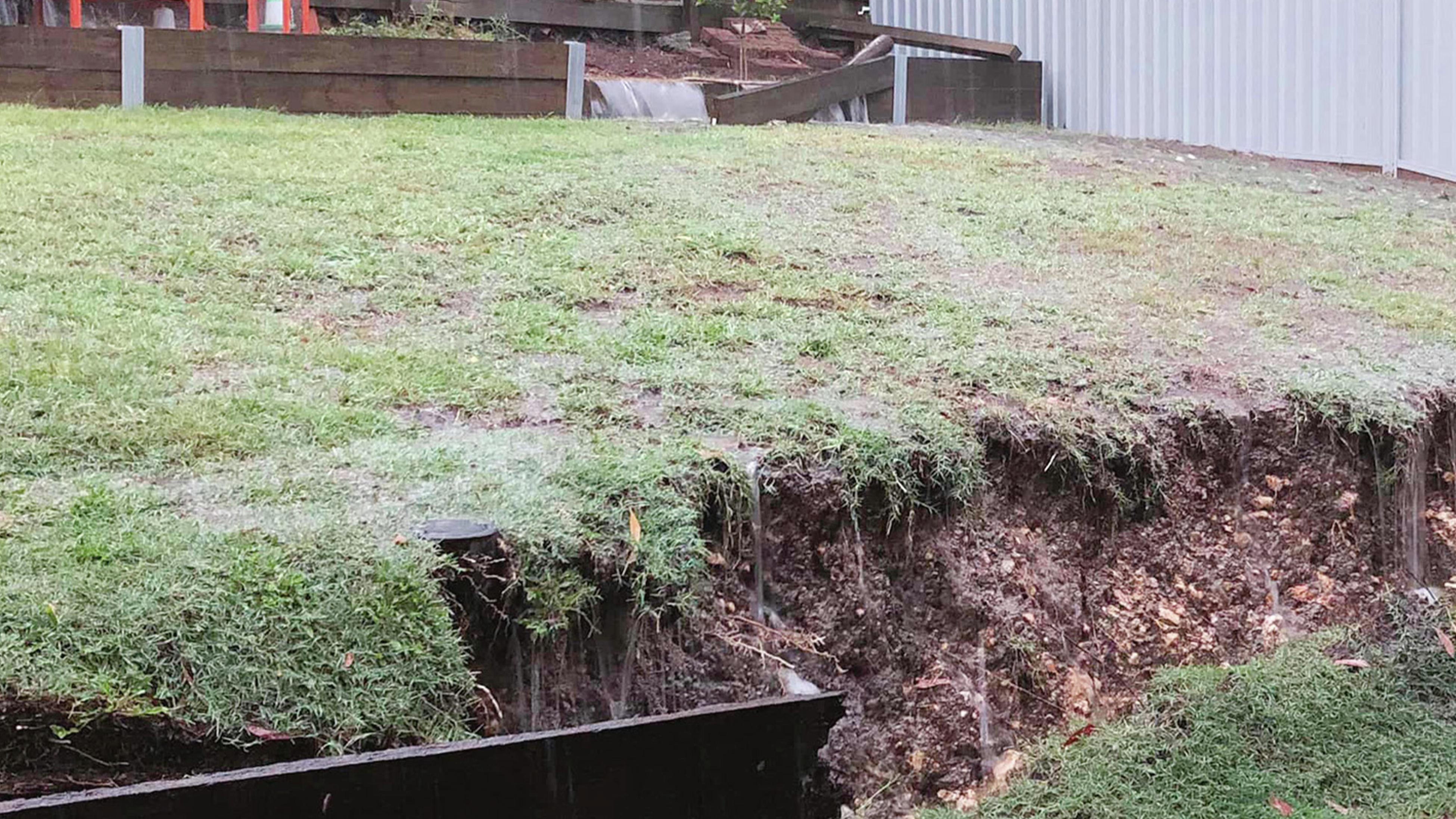 A sloping backyard with a large ditch dug out of it at the bottom