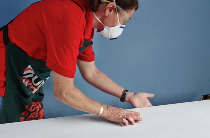 Person wearing a mask sanding a door that is lying horizontal on supports