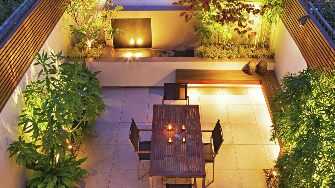 An aerial view of an outdoor room with lighting behind plants, under bench seats and overhead