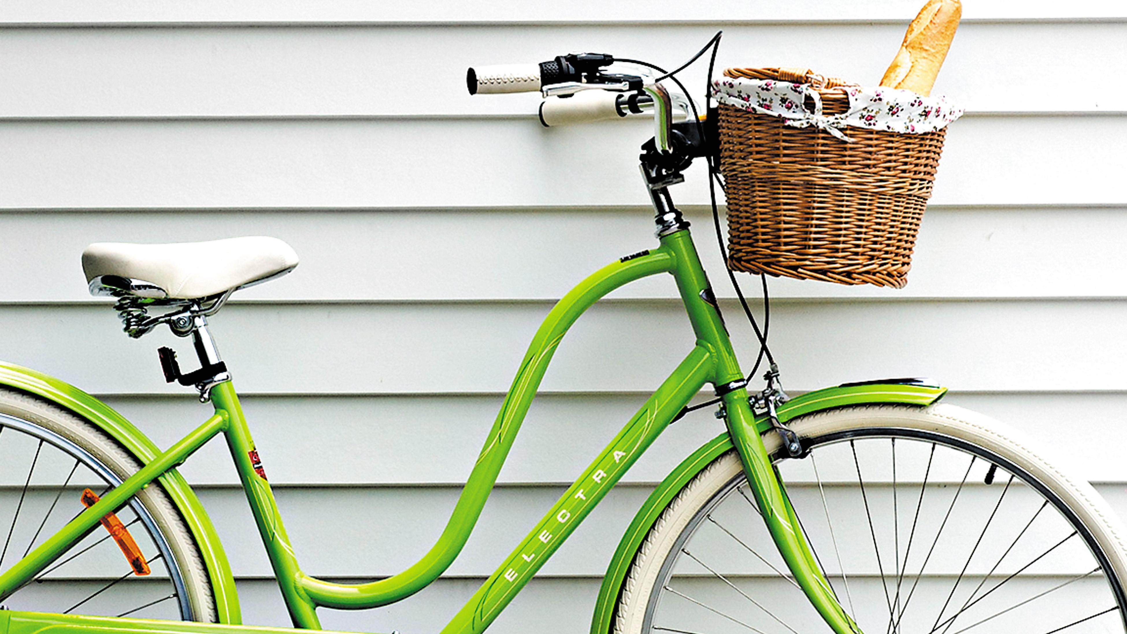 A green bike leaning up against a white weatherboard house.
