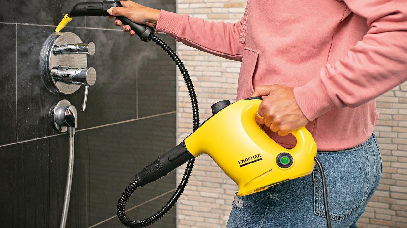 A woman uses a Kärcher steam cleaner to remove grime from a shower mixer