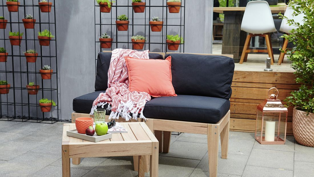 Two outdoor chairs with cushions and throw rug positioned near a wooden coffee table, in an outdoor setting including two wire mesh vertical gardens