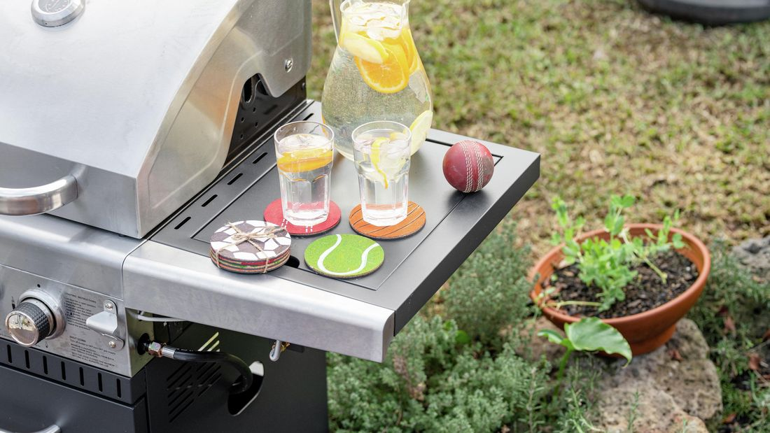 Two drinks placed on coasters which resemble ball sports, sitting on a BBQ's sidetable