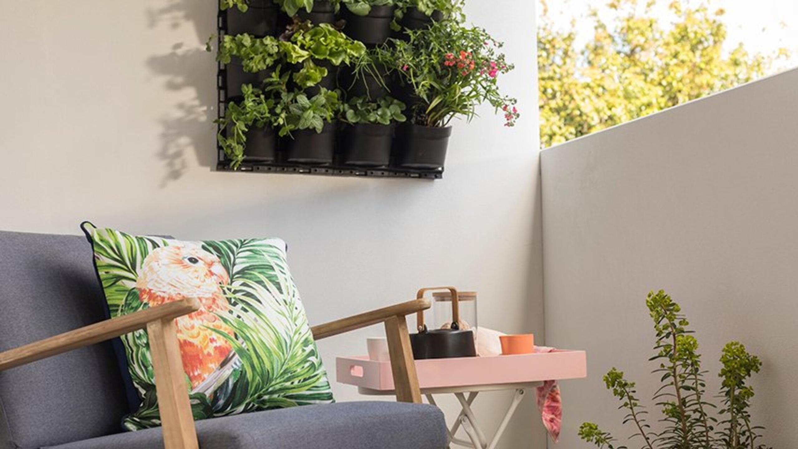 Outdoor lounge with vertical garden on white wall in the background.