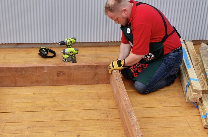 Person lining up two thick pieces of timber together in an L-shape.