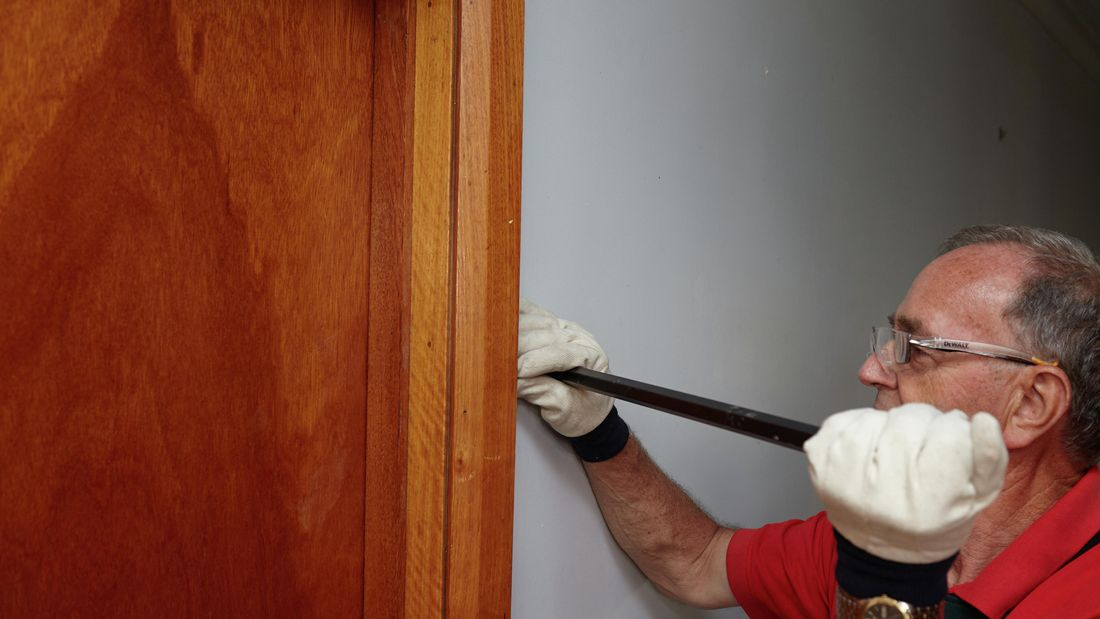 A Bunnings team member using a pry bar to remove an architrave